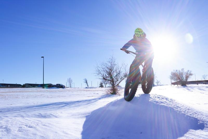 31/54: Woman rides a bike in the snow